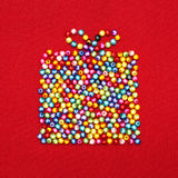 Gift box made of colorful beads on red Royalty Free Stock Image