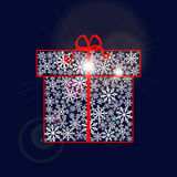 Gift box made of snowflakes with red ribbon and bow on dark blue background. Royalty Free Stock Photos