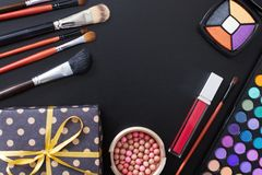 Gift box and makeup tools and accessories isolated on black background. Top view and mock up. Lipstick, eye shadows, make up brush. Es. Beauty product royalty free stock photos