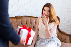 Gift box in male hands and surprised woman Stock Photo