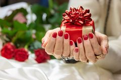 Gift box in manicured female hands. Royalty Free Stock Images