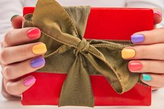 Gift box in manicured female hands. Royalty Free Stock Photo