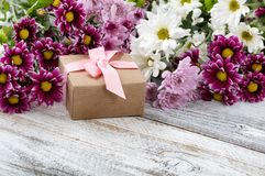Gift box with mixed flowers in background on white weathered woo Royalty Free Stock Image