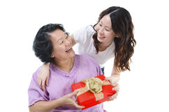 Gift box for mother. Celebrating mothers day or birthday. Portrait of Asian senior parent getting a present box from adult daughter, isolated on white background Royalty Free Stock Photography