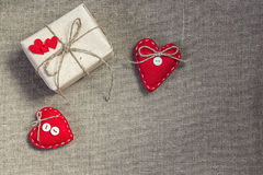 Gift box with a natural rope and two red hearts on sacking Royalty Free Stock Images