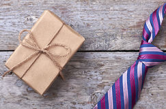 Gift box near striped necktie. Tie on wooden surface. How to choose a present royalty free stock photography