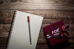 Gift box, notebook and pen on wooden plank Royalty Free Stock Image