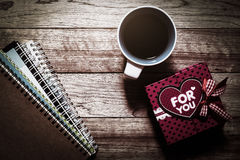 Gift box, notebooks and coffee on wooden plank Stock Images