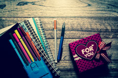 Gift box, notebooks and pens on wooden plank. Under light in vintage style stock photos
