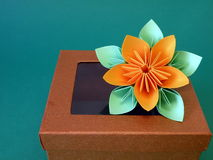 Gift box and origami flower. Brown gift box and origami flower royalty free stock image