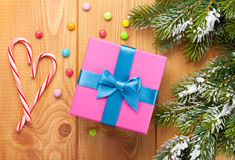 Gift box over christmas wooden background with snow fir tree Stock Photo
