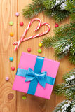 Gift box over christmas wooden background with snow fir tree Stock Photography