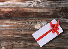 Gift box over wooden background. Gift box with red ribbon over wooden background Stock Images