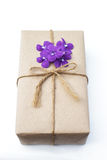 Gift box package wrapped with paper and rope with purple flowers Royalty Free Stock Images