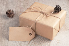 Gift box packed brown paper and twine with blank tag decorated fir cones on white wooden table Royalty Free Stock Photos