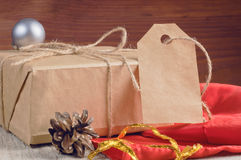 Gift box packed brown paper and twine with blank tag decorated holiday accessories on wooden table Royalty Free Stock Image