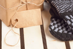 Gift box packed brown paper and twine with blank tag and  handmade mittens nearby on wooden grid panel Stock Images