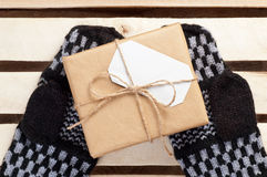 Gift box packed brown paper and twine with blank white address card on handmade mittens lying on wooden grid panel top view Stock Image