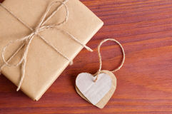 Gift box packed brown paper and twine with two cardboard hearts tied together top view on wooden table with space for text Stock Images