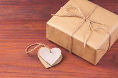 Gift box packed brown paper and twine with two cardboard hearts tied together on wooden table with space for text Royalty Free Stock Photography