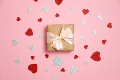 Gift box packed in kraft paper with ribbon bow and red and grey heart shaped valentines card lay on p. Valentines day composition : gift box packed in kraft stock photos