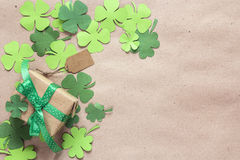 Gift box with paper clover leaves on the brown paper. St.Patrick royalty free stock images