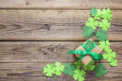 Gift box with paper clover leaves on the old wooden background. Royalty Free Stock Photo