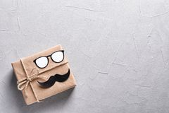 Gift box with paper glasses and moustache. On grey background, top view royalty free stock photos