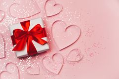Gift box and paper hearts with sparkling glitter on pink background. Romantic st. Valentine`s day concept of greetings. Top view, flat lay Royalty Free Stock Images