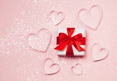 Gift box and paper hearts with sparkling glitter on pink background. Romantic st. Valentine`s day concept of greetings. Top view, flat lay Royalty Free Stock Image