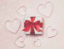 Gift box and paper hearts with sparkling glitter on pink background. Romantic st. Valentine`s day concept of greetings. Top view,. Flat lay Royalty Free Stock Image