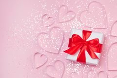 Gift box and paper hearts with sparkling glitter on pink background. Romantic st. Valentine`s day concept of greetings. Top view,. Flat lay Royalty Free Stock Images