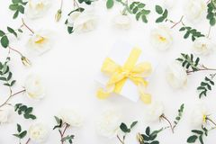 Gift box and pastel rose flowers decorated green leaves on white table top view. Flat lay style. Stock Images