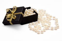 Gift box with pearl beads. Gift box with golden ribbon and pearl beads isolated on white background Stock Images