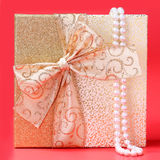 Gift Box with Pearl Necklace over red background. Christmas Stock Photo