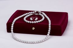 Gift box and pearls set. Pearls set with a gift box on white background. The pearl gift set consists in 3 pieces: necklace,earrings and a bracelet Stock Photos