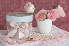 Gift box, pearls, wedding rings and roses. A still life of a gift box with pearls, wedding rings and pink roses in a white vase Stock Photography