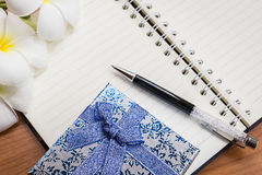 Gift box and pen on notebook Stock Images