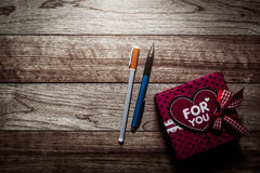 Gift box and pens on wooden plank. Under light in vintage style stock photo