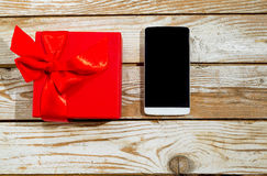 Gift box and phone on wood background Stock Images