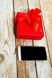 Gift box and phone on wood background Stock Photography