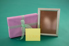 Gift box, photo frame with text mom on card against green background Stock Photography