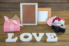 Gift box, photo frame, vintage camera and flower vase. On wooden plank Stock Photos