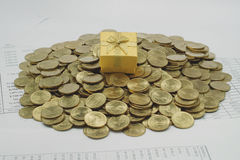 Gift box on a pile of gold coins Stock Image