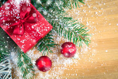 Gift box with pine branch, red Christmas balls and snow Royalty Free Stock Photos