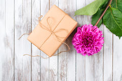 Gift box and pink blooming chrysanthemum flower on wooden background. Space for text. Stock Photo