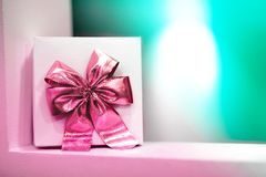 Gift box with pink bow on a blue background stock photo