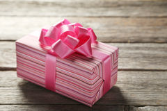 Gift box with pink bow on grey wooden background Stock Image