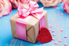 Gift box with pink bow ribbon and glitter hearts on blue spring background Royalty Free Stock Images