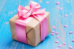 Gift box with pink bow ribbon and glitter hearts on blue spring background Stock Photos